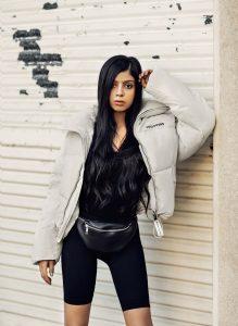 girl wearing windbreaker against a wall